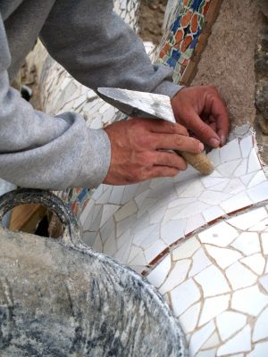 Hands and trowel cementing mosaic tiles in place
